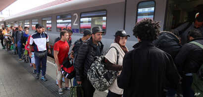 Migrants and refugees board  a train from Vienna to Salzburg at the Westbahnhof train station in Vienna, Sept. 19, 2015.