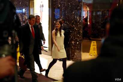 U.S. Sen. Joe Manchin, a Democrat from West Virginia, is escorted past security by a Trump aide, at Trump Tower in New York, Dec. 12, 2016. (R. Taylor/VOA)