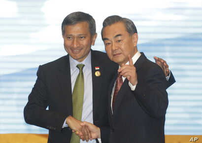 FILE - Singapore's Foreign Minister Vivian Balakrishnan, left, shakes hands with Chinese Foreign Minister Wang Yi, right before they pose for a photo during the ASEAN – China Foreign Ministers' Meeting in Vientiane, Laos, July 25, 2016.