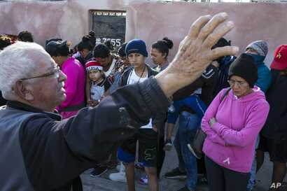 """A volunteer who helped with the delivery of a donated breakfast prays as Central American migrants wait in a line to receive the breakfast at a temporary shelter in Tijuana, Mexico, Nov. 17, 2018.  The mayor has called the migrants' arrival an """"avala..."""