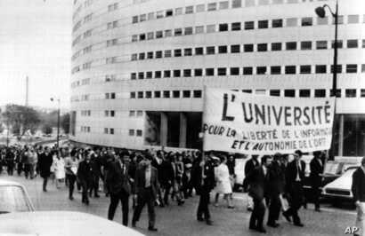 FILE - Paris students march on June 9, 1968, around the French Maison de la Radio in support of the striking TV and radio employees. The banner reads The University for the Liberty of News and the Autonomy of the ORTF (the Government controlled TV an...