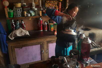 FILE - A Nepalese woman prepares tea in a refuge for mountaineers in the Khumbu Valley in the Everest region of Nepal, April 14, 2016.