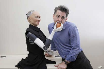FILE - David Hanson, the founder of Hanson Robotics, poses with his company's flagship robot, Sophia, a lifelike robot powered by artificial intelligence, in Hong Kong, Sept. 28, 2017.