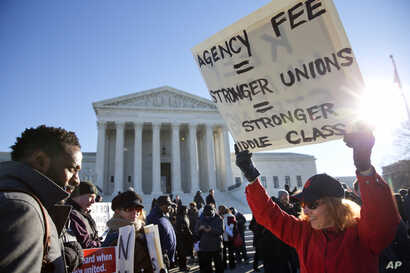 Lesa Curtis of Westchester, N.Y., (R), who is pro agency fees and a former president of her union, rallies outside the Supreme Court in Washington, Jan. 11, 2016.