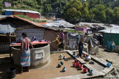 Rohingya Muslim men collect water from a well at Unchiprang refugee camp near Cox's Bazar, in Bangladesh, Nov. 16, 2018.