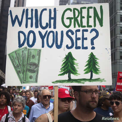 """A protester carries a sign during the """"People's Climate March"""" in the Manhattan borough of New York September 21, 2014."""
