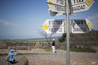 Tourists pose for photograph next to a mock road sign for Damascus, the capital of Syria, and other capitals and cities and a cutout of a soldier, in an old outpost in the Israeli controlled Golan Heights near the border with Syria, March 22, 2019.