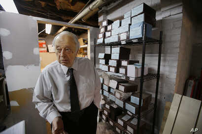 Peter Stefan, funeral director and proprietor of the Graham Putnam & Mahoney Funeral Parlor, stands in front of shelves holding the cremated remains of unclaimed bodies dating back more then a decade, in the basement of the Graham Putnam & Mahoney Fu...