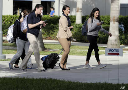 "Students walk past a ""Vote"" sign next to an early voting site on the Florida International University campus, Oct. 23, 2018, in Miami."