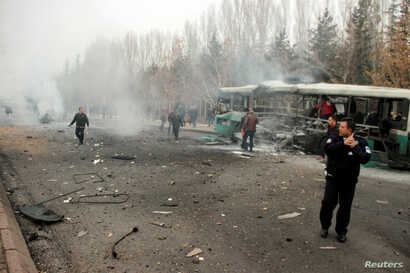 People react to a bus that was hit by an explosion in Kayseri, Turkey, Dec. 17, 2016.