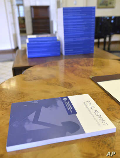 Volumes of the Final Report of the Royal Commission into Institutional Responses to Child Sexual Abuse sit on a table at Government House, in Canberra, Dec. 15, 2017. The commission delivered its final 17-volume report and 189 recommendations followi...