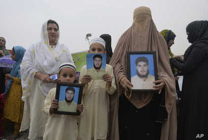 A family from a Pakistani tribal area display pictures of a missing family member during a rally in the northwestern city of Peshawar, Pakistan, Apr. 8, 2018.
