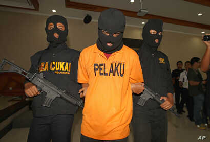 А suspected drug smuggler, his face obscured with a mask, is escorted by Indonesian Customs officers in Bali, Indonesia, Apr. 27, 2016.