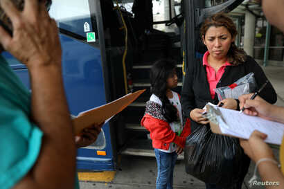 A migrant and her daughter prepare to take a bus after being released from a detention center, in McAllen, Texas, May 9, 2017.
