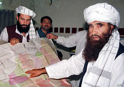 A 2001 file photo of Jalaluddin Haqqani (R), Leader of the Haqqani Network, pointing to a map of Afghanistan during a visit to Islamabad, Pakistan while his son Naziruddin (L) looks on