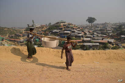 Rohingya refugees carry a hume pipe in Balukhali refugee camp near Cox's Bazar, in Bangladesh, Nov. 17, 2018.