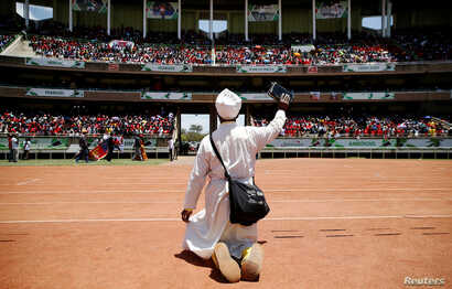 A supporter prays before the arrival of Kenya's President Uhuru Kenyatta at the Kasarani stadium for the official launch of the Jubilee Party ahead of the 2017 general elections in Kenya's capital Nairobi, Sept. 10, 2016.