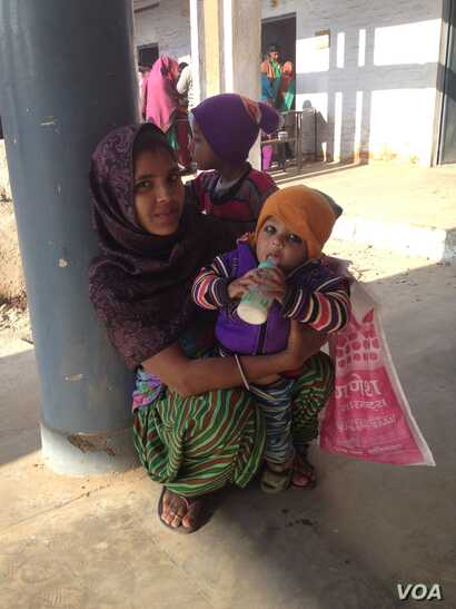 Suman, who goes by one name only, is waiting at a polling station with her two young children and says she will stamp on the flower - the lotus symbol of the Bharatiya Janata Party. (A. Pasricha/VOA)