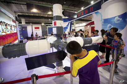 FILE - Visitors look at a model of China's Tiangong-1 space station at the China Beijing International High-Tech Expo in Beijing, June 10, 2017.