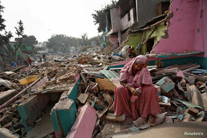 A woman reacts amid the rubble of her home in a slum which was razed to the ground by local authorities in a bid to relocate the residents, Delhi, India, November 2, 2017.