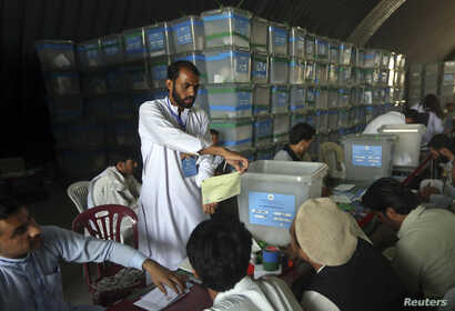 Afghan election workers count ballot papers for an audit of the presidential run-off in Kabul, Afghanistan, Aug. 6, 2014.