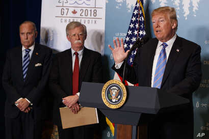 White House chief economic adviser Larry Kudlow, left, and National Security Adviser John Bolton look on as President Donald Trump speaks during a news conference at the G-7 summit, Saturday, June 9, 2018, in La Malbaie, Quebec, Canada.