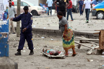 A woman looks at the body of a man killed during election protests in Kinshasa, Democratic Republic of Congo, Monday, Sept. 19, 2016.