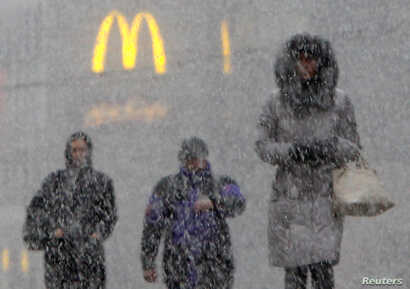 People walk under heavy snow in central Moscow — with a familiar logo in the background, Nov. 11, 2011.
