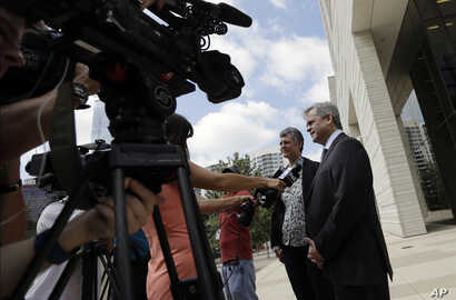 "Austin Mayor Steve Adler, right, and Travis County Judge Sarah Eckhardt talk with reporters outside the federal courthouse, June 29, 2017, in Austin, Texas. A new Texas ""sanctuary city"" ban is back in court as the state asks a federal judge to approv..."