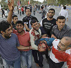 Bahrainis carry a wounded anti-government protester in Manama during the first wave of the crackdown, February 18, 2011