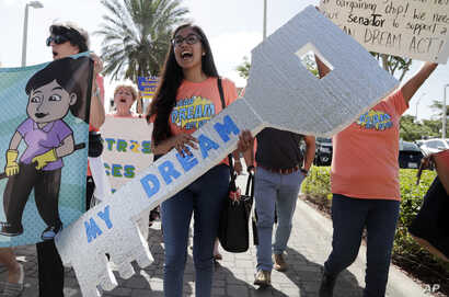 "FILE-Maria Angelica Ramirez carries a large key reading ""My Dream"" during a protest outside the office of Sen. Marco Rubio, R-Fla., in support of Deferred Action for Childhood Arrivals (DACA), and Congress passing a clean Dream Act."