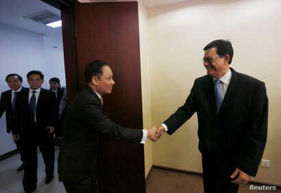 Var Kim Hong (R) shakes hands with Vietnamese Deputy Foreign Minister Le Hoai Trung