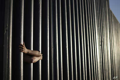 FILE - In this June 13, 2013, photo, hands from Daniel Zambrano of Tijuana, Mexico, hold on to the bars that make up the border wall separating the U.S. and Mexico as the border meets the Pacific Ocean in San Diego.