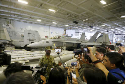 With fighter jets in the background, Lt. Cmdr. Tim Hawkins talks to the media on board the USS Carl Vinson aircraft carrier anchored off Manila, Philippines, for a five-day port call along with guided-missile destroyer USS Michael Murphy, Feb. 17, 20...