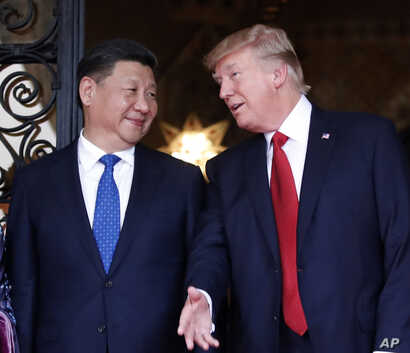 FILE -  Chinese President Xi Jinping, left, smiles at U.S. President Donald Trump as they pose together with their wives for photographers before dinner at Mar-a-Lago in Palm Beach, Fla.