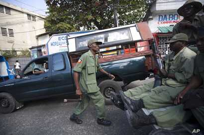 Armed, former members of Haiti's disbanded army patrol the streets while simultaneous pro- and anti-government protests take place in Port-au-Prince, Haiti, Feb. 5, 2016.