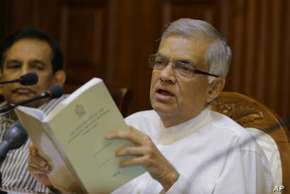 Sri Lanka's sacked prime minister Ranil Wickremesinghe holds a copy of the constitution of Sri Lanka as he attends a media briefing at his official residence in Colombo, Sri Lanka, Oct. 29, 2018.