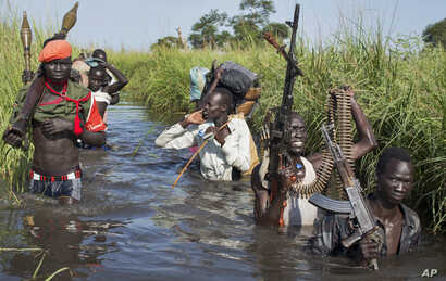 FILE - Rebel soldiers are seen protecting civilians from the Nuer ethnic group as they walk through flooded areas to reach a makeshift U.N. camp for the displaced in the town of Bentiu, South Sudan, Sept. 20, 2014.