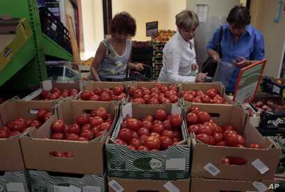 Women choose Dutch tomatoes at a supermarket in downtown Moscow on Thursday, Aug. 7, 2014. The Russian government has banned all imports of meat, fish, milk and milk products and fruit and vegetables from the United States, the European Union, Austra