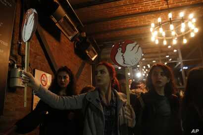 Protesters hold placards as they take cover at a shop after Turkish police fired tear gas on Istiklal, the main shopping street, in Istanbul, during International Women's Day, March 8, 2019.