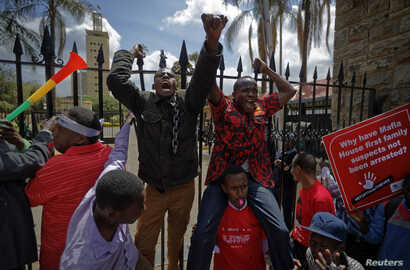 Protesters briefly climb the gates of Parliament, one holding a placard referring to President Uhuru Kenyatta, during an anti-corruption demonstration in Nairobi, Kenya, May 31, 2018.
