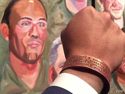 """Johnnie Yellock holds his hand next to his portrait painted by former president George W. Bush. The bracelet on Yellock's hand bears the names of four of his personal heroes. """"Those that don't come home ... those are the heroes of our time,"""" he..."""