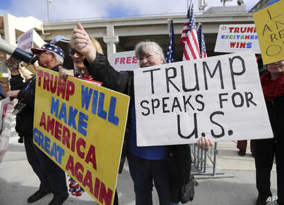 A woman gives a thumbs up as people in a passing car honk as demonstrators in favor of President Donald Trump's executive order banning travel to the U.S. from seven primarily Muslim nations stand across the street from the Tom Bradley International ...