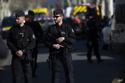 French police officers cordon off the area around a terrorist attack in Trebes, southern France, March 23, 2018.