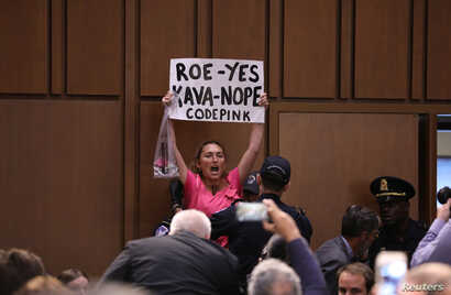 A protester is removed during the start of U.S. Supreme Court nominee judge Brett Kavanaugh's Senate Judiciary Committee confirmation hearing on Capitol Hill in Washington, Sept. 4, 2018.