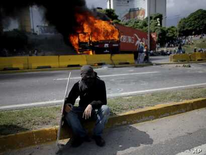 A demonstrator rests near a burning truck during a protest on the Francisco Fajardo highway outside La Carlota Air Base in Caracas, Venezuela, June 23, 2017.