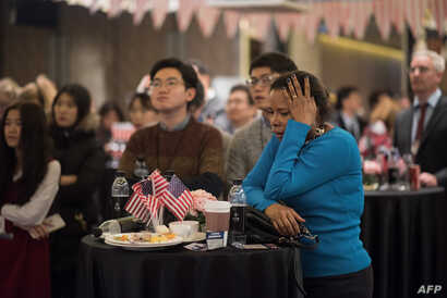 People watch a screen showing coverage of the US presidential election at an election event organized by the US Embassy, at a hotel in Seoul, Nov.  9, 2016.