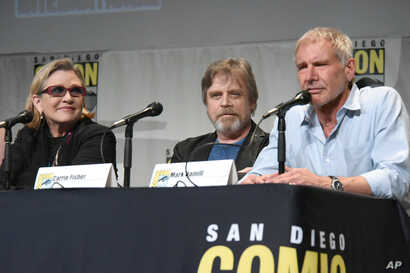 """FILE - Carrie Fisher, Mark Hamill, and Harrison Ford attend Lucasfilm's """"Star Wars: The Force Awakens"""" panel on day 2 of Comic-Con International in San Diego, Calif., July 10, 2015."""