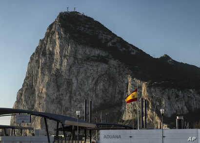 FILE - In this March 1, 2017 photo, a Spanish flag flies on top of the customs house on the Spanish side of the border between Spain and the British overseas territory of Gibraltar with the Rock as a background, in La Linea de la Concepcion, Southern...