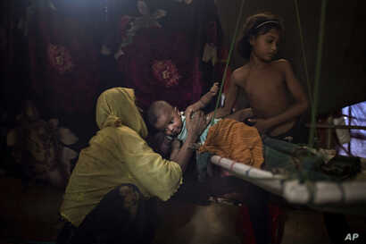 """M's daughter  hands over her baby brother to their mother in their shelter in Kutupalong refugee camp, June 26, 2018. """"M"""" was raped by six soldiers from Myanmar's security forces after they strangled her 2-year-old son to death."""